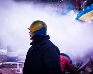 A Pro-European activist with helmet at a barricade during that the Riot police stormed Kiev protest camp in early morning. dec 11th 2013. Demonstration in Kiev against Ukraine's rejection of the EU agreement