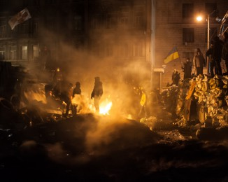 Protesters stand on night watch atop three rows of barricades now closing Hrushevskoho street during standoff with the riot police, on January 23, 2014 in Kiev, Ukraine.