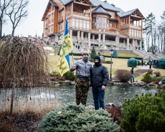 Visitors wave an Ukrainain flag in the garden in front of the lavish mansion built by the former President Yanukovych on February 23, 2014 in Kyiv, Ukraine.