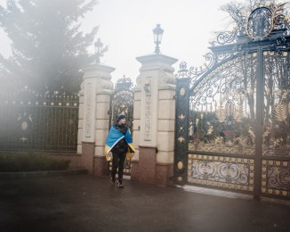 A visitor with the ukrainian flag looks at one of the gates of the residence compound of former Ukrainian President Viktor Yanukovych's residency in Mezhygirya, near Kiev on February 23, 2014 in Kyiv, Ukraine.