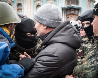 maidan self-defense group members are talking with a man in front of the ukrainian parliament. Anti-government protesters take control   of the Rada building, the Ukrainian parliament while an exceptional session is called on February 23, 2014 in Kyiv, Ukraine. february 22th. 2014. Kyiv. Ukraine.