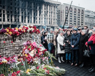 People lay carnations at a makeshift memorial to the victims of the past weeks' riots on Institutska street in central Kiev on February 23, 2014 in Kyiv, Ukraine.