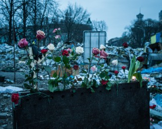 People lay carnations at a makeshift memorial to the victims of the past weeks' riots on Institutska street behind the Ukraine hotel on February 23, 2014 in Kyiv, Ukraine.