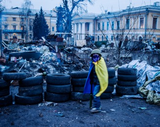 a child dressed like a Maidan hero, visites places where was the bloody repression against the anti-government protestors . Instytuts'ka street. october palace. Kyiv. Ukraine. february 22th. 2014.