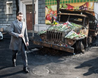A man walks by a charred truck covered with flowers on the spot of previous deadly clashes between anti-government protesters and the riot police on February 24, 2014 in Kyiv. Ukraine.