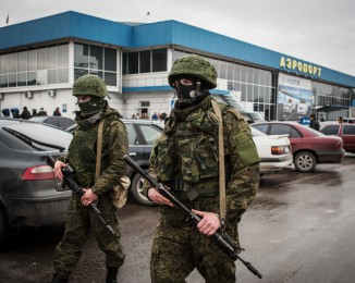 Soldiers, who were wearing no identifying insignia and declined to say whether they were Russian or Ukrainian, patrol outside the Simferopol International Airport after a pro-Russian crowd had gathered on February 28, 2014 Simferopol, Ukraine. Crimea.