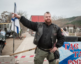 A pro-Russian militant and member of the 'Night Wolves' Crimean biker club helps man a checkpoint on a road leading to Sevastopol in Crimea on March 2, 2014 near Verkhn'osadove, Ukraine.