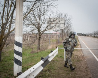 Crimean civilian self-defense member guard the road to the Russian occupied Belbek airbase as Russian-led troops blockade a number of Ukrainian military bases across Crimea, on March 4, 2014 in Lubimovka, Ukraine.