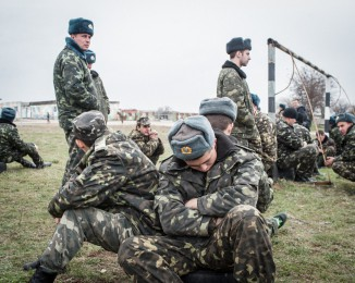 Unarmed Ukrainian troops rest on the Belbek airfield after they confronted soldiers under Russian command occupying the base in Crimea on March 4, 2014 in Lubimovka, Ukraine. The Ukrainians are stationed at their garrison nearby, and after spending a tense night anticipating a Russian attack following the expiration of a Russian deadline to surrender, in which family members of troops spent the night at the garrison gate in support of the soldiers, their commander Colonel Yuli Mamchor announced his bold plan this morning to retake the airfield by confronting the Russian-lead soldiers unarmed. The Russian-lead troops fired their weapons into the air but then granted Mamchor the beginning of negotiations with their commander. Russian-lead troops have blockaded a number of Ukrainian military bases across Crimea.