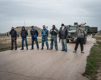 Crimean civilian self-defense members guard the Russian occupied Belbek airbase as Russian-led troops blockade a number of Ukrainian military bases across Crimea, on March 4, 2014 in Lubimovka, Ukraine. Ukrainians troops, stationed at their garrison nearby, confronted the Russian soldiers unarmed today. The Russian-led troops fired their weapons into the air but then granted Colonel Yuli Mamchor, commander of the Ukrainian military, negotiations with their commander.
