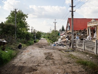 AVDIIVKA - Lermontova Street-May 24th, 2017- 5:27 PM A man looks at his neighbor's house destroyed the day before by shelling in the old town of Avdiivka.